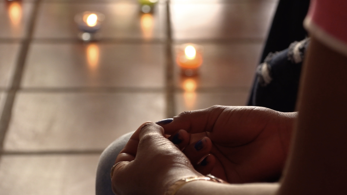 In the foreground a pair of hands sit in a lap. The background is made up of a tiled floor and tea-light candles
